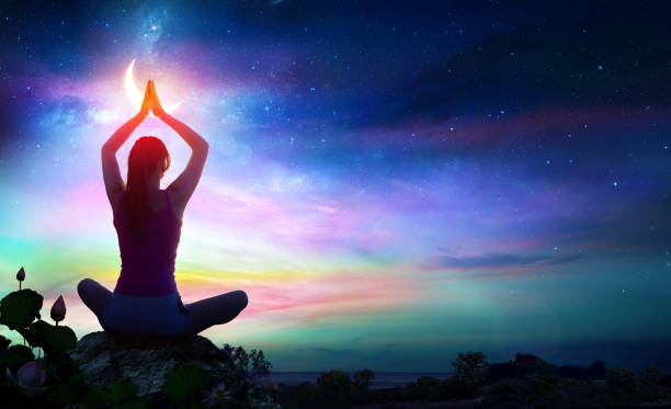 Woman Doing Yoga With Lotus Flowers And Rainbow Gradient In The Sky At Night